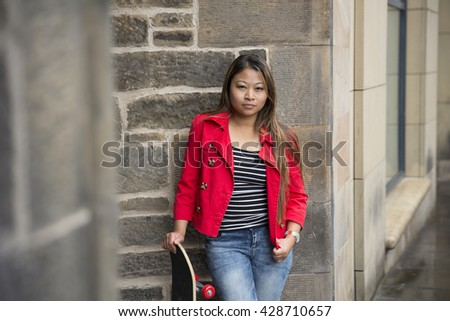 Portrait of a Filipino woman holding skateboard and leaning against a wall.