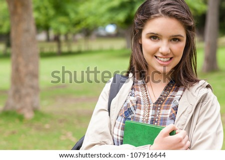 Portrait of a first-year student holding a textbook while posing in a park - stock photo