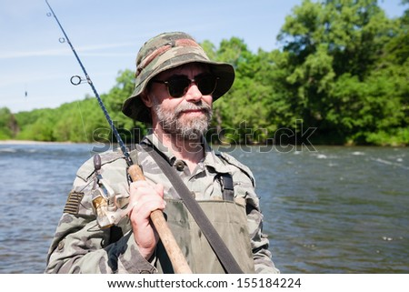 Portrait of a fisherman on a fishing trip on the river. - stock photo