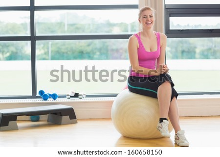 Portrait of a fit cheerful young woman sitting on exercise ball in fitness studio