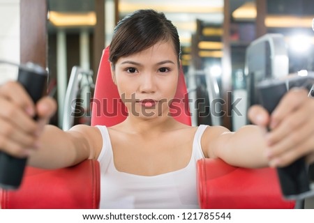 Portrait of a fit girl with intense look working out in the gym - stock photo