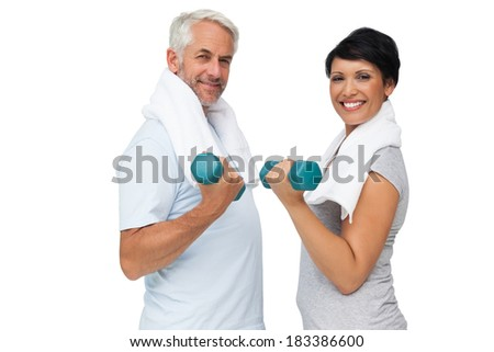 Portrait of a fit mature couple exercising with dumbbells over white background - stock photo