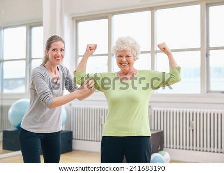 Portrait of a fit old woman flexing her arms and showing her muscles with personal trainer at gym - stock photo