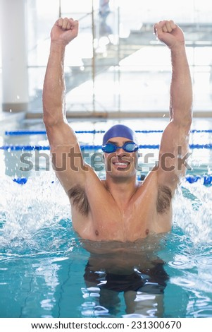 Portrait of a fit swimmer cheering in the pool at leisure center - stock photo