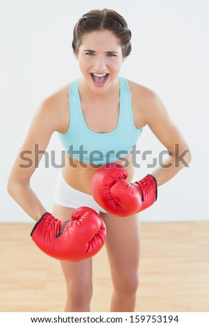 Portrait of a fit woman in red boxing gloves flexing muscles at fitness studio