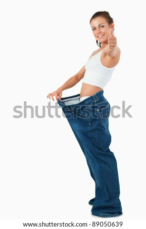Portrait of a fit woman wearing too large pants with the thumb up against a white background - stock photo