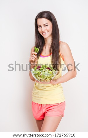 Portrait of a fit young brunette woman having a healthy salad.