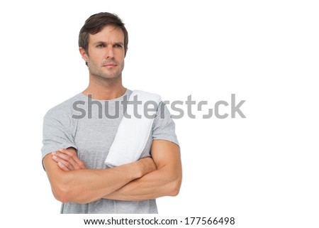 Portrait of a fit young man with towel standing over white background
