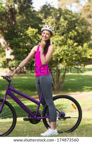 Portrait of a fit young woman with helmet and bicycle at the park - stock photo