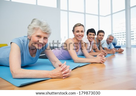 Portrait of a fitness group lying in row at the yoga class - stock photo