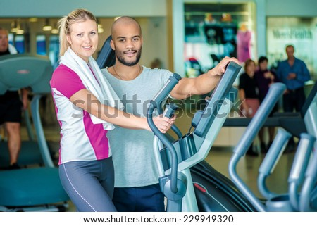Portrait of a fitness instructor and sportswomen. Young smiling fitness instructor standing near trainer - stock photo