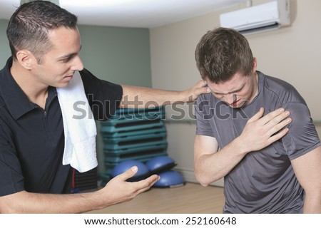 Portrait of a fitness man reaching for his knee in pain - stock photo