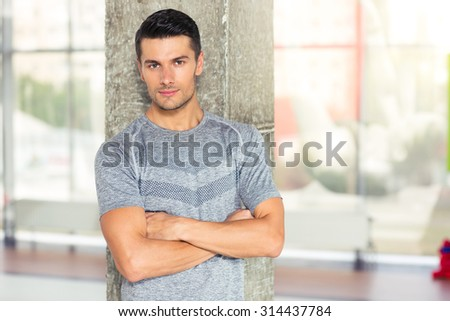 Portrait of a fitness man standing with arms folded in gym and looking at camera