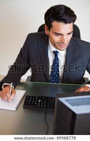 Portrait of a focused businessman taking notes in his office - stock photo