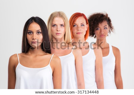 Portrait of a four serious women with colourful hair standing in a raw isolated on a white background - stock photo