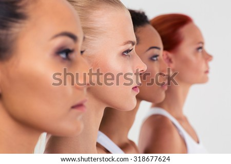 Portrait of a four women standing in a raw isolated on a white background - stock photo