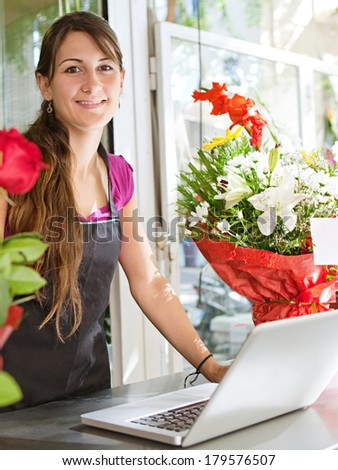 Portrait of a friendly and welcoming florist business woman owner proudly standing at the counter of a flower store using a laptop computer, smiling. Small business technology.