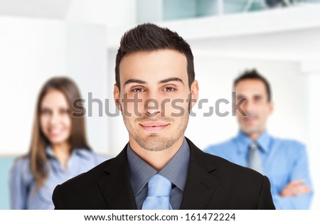 Portrait of a friendly businessman in front of his team - stock photo