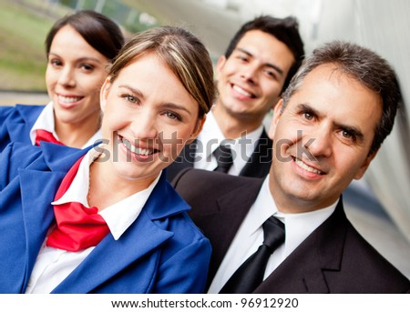 Portrait of a friendly group of pilots and air hostesses smiling - stock photo