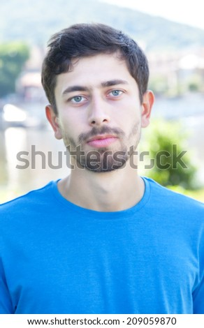 Portrait of a friendly guy with beard outside - stock photo