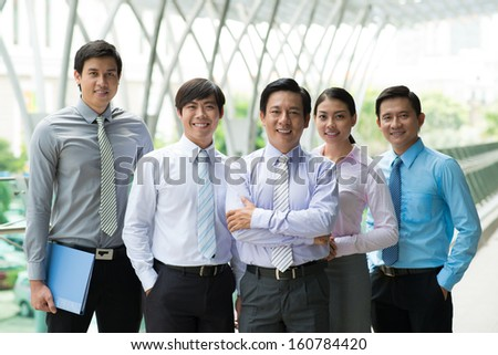 Portrait of a friendly modern business team smiling and looking at camera - stock photo