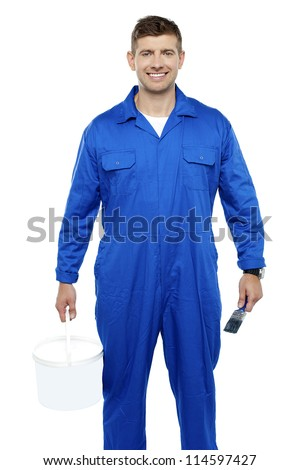 Portrait of a friendly painter holding bucket and paint brush isolated on white