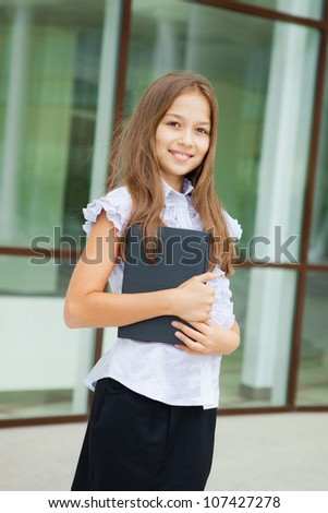 Portrait of a friendly school girl student standing in school uniform and holding book