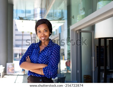 Portrait of a friendly smiling business woman standing outside in the city - stock photo
