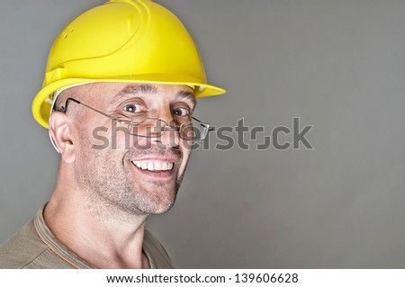 Portrait of a friendly smiling senior worker with yellow hard hat - stock photo
