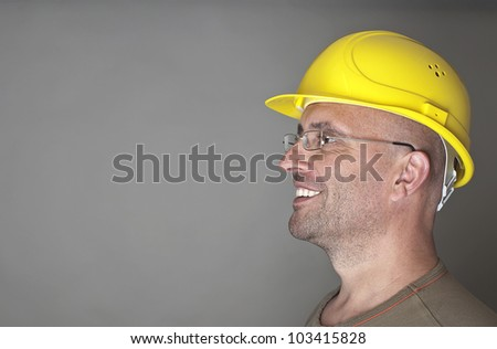 Portrait of a friendly smiling worker with helmet - stock photo