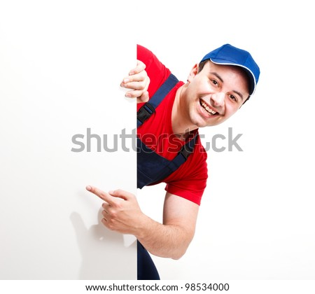 Portrait of a friendly worker pointing his finger to a blank board - stock photo
