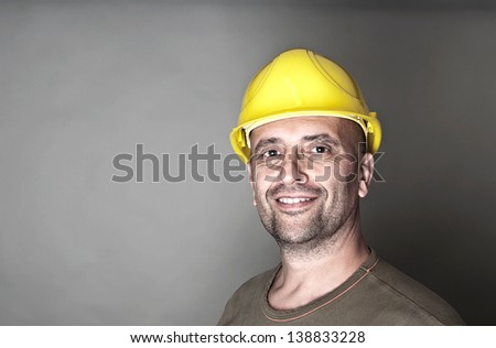 Portrait of a friendly worker with yellow hard hat