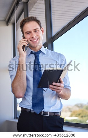 Portrait of a friendly young businessman standing in his office with his diary open in his hand, smiling at the camera while holding his mobile phone to his ear - stock photo