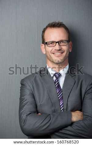 Portrait of a friendly young businessman with arms crossed leaning against a gray wall - stock photo