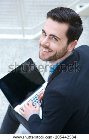 Portrait of a friendly young man working on laptop - stock photo
