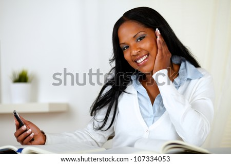 Portrait of a friendly young woman looking to you while holding a cellphone in one hand at home indoor