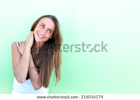 Portrait of a friendly young woman smiling on green background