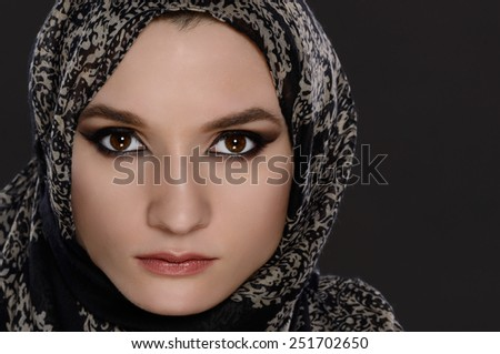 Portrait of a front view of a beautiful arab woman face with a head scarf on a gray background - stock photo