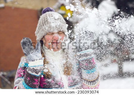 Portrait of a frowning young woman in the middle of a snowball fight getting a snowball in her face - stock photo