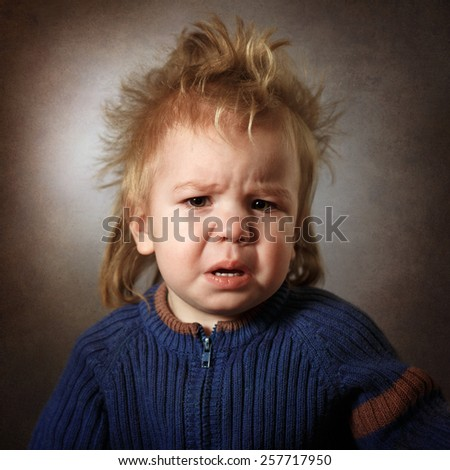 portrait of a frustrated baby on a dark background - stock photo