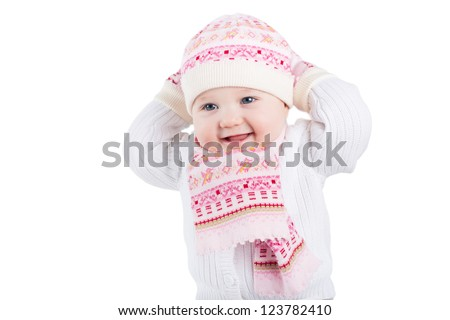 Portrait of a funny baby girl in a knitted hat, scarf and mitten, isolated on white - stock photo