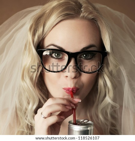 portrait of a funny beautiful hipster bride drinking something from tin can through red plastic sipper. daylight. studio shot