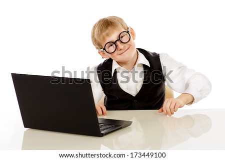 Portrait of a funny boy in a suit and round glasses sitting with his laptop. Isolated over white. - stock photo