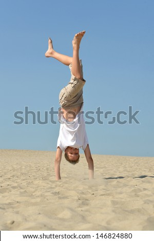 Portrait of a funny boy standing on his hands in the sand - stock photo