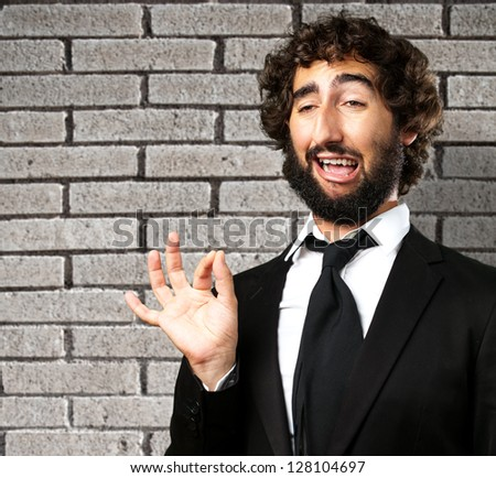 Portrait Of A Funny Businessman against a grey brick wall