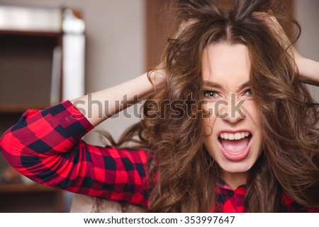 Portrait of a funny cheerful woman touching her hair