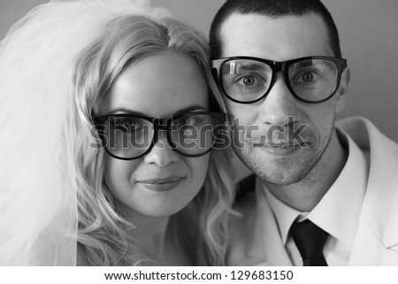 Portrait of a funny handsome hipster family (bride and groom) posing in trendy glasses together on their wedding day. daylight. studio shot - stock photo