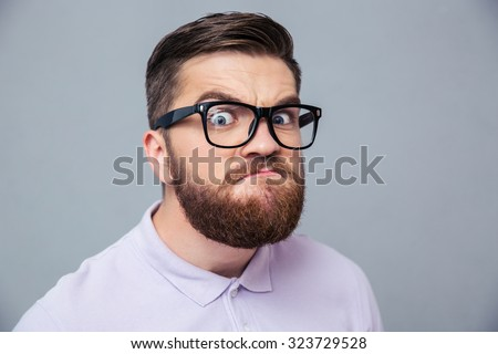 Portrait of a funny hipster man looking at camera over gray background - stock photo