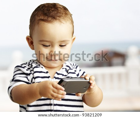 portrait of a funny kid playing with a mobile near the beach - stock photo