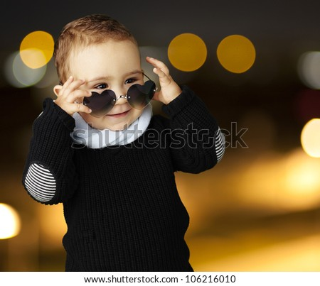 portrait of a funny kid wearing heart sunglasses at a city by night - stock photo